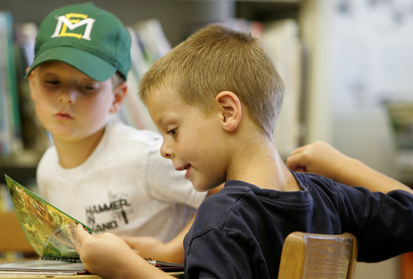 Essex: T.J. Rogers, 5, reads about fun recipes in a Star Wars cookbook with his twin brother Tristan at the TOHP Burnham Library Wednesday afternoon. The boys came to the library with their mom and sister Hailey, 4, to pick out books from the summer reading list, which did not include this cookbook. Mary Muckenhoupt/Gloucester Daily Times