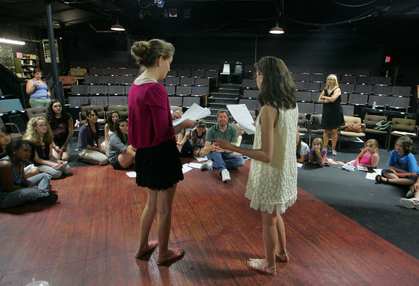 "Gloucester: Devon Harmon, 17, left, and Caroline Zola, 15, read ""The Boston Milk Party"" wriiten by playwrite Kelly Younger, sitting center, during a Youth Acting Workshop run by Heidi Dalin at the Gloucester Stage Company Friday afternoon.  The  Summer Session of Youth Acting Workshops is for children ages 6 to 18.  The six week acting training program encourages students to discover and nurture their creative potential. Mary Muckenhoupt/Gloucester Daily Times"