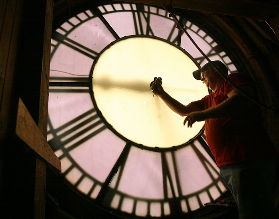 Gloucester: Tom Moore of Moore's Steeple People removes the old mechanical elements in preparation to remove the hands from one of the clock faces at Gloucester City Hall yesterday. The clocks are getting new hands and new motors as part of the building's restoration project. Photo by Kate Glass/Gloucester Daily Times