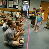 Gloucester: Children at the Sawyer Free Library join the Vic and Sticks Recycled Rhythm Band on Wednesday morning. The kids played instruements made from recycled bottles, cans, buckets and other objects. Photo by Kate Glass/Gloucester Daily Times