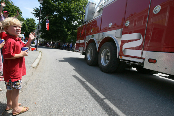 Manchester: Wyatt Riehl, 5, waves to the Manchester Firefighters during the Manchester 4th of July Parade yesterday afternoon. Photo by Kate Glass/Gloucester Daily Times