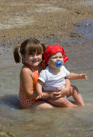 Gloucester: Allie Rose Nicastro, 5, holds her sister Mylee Grace, 9 months, as they try and stay cool at the water's edge while spending the day at Nile Beach Wednesday afternoon. Mary Muckenhoupt/Gloucester Daily Times