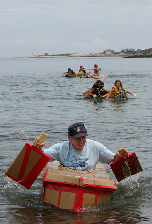 Rockport: Jack Munrois the first to row to shore in his cardboard during the annual Race to the Bottom at Back Beach Saturday afternoon.  The race, put on by the Tyrian-Ashler-Acacia Lodge as a fundraiser, requires its participants to build a boat using only certain items such as cardboard, a 25 ft. rop, duct tape, and a can of schalak. Ten boats were in this years race and all but a few didn't make it. Mary Muckenhoupt/Gloucester Daily Times
