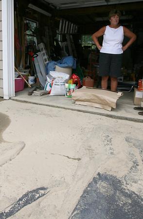 Gloucester: Sharon Lovasco looks out at the dirt that washed into her driveway and garage from a water main break across the street from her Washington Street home yesterday morning. Photo by Kate Glass/Gloucester Daily Times