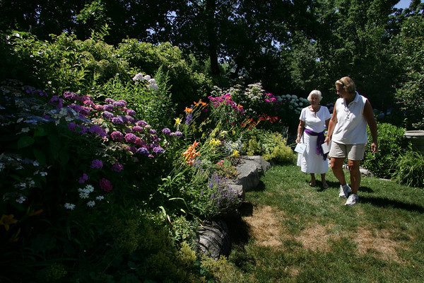 "Rockport: Jean Goldsberry and her daughter Amy Robinson of Rockport walk through a garden on Gott St during the Rockport Garden Clubs Coastal Garden Tour Saturday afternoon.  ""It always amazes me how many hidden gardens there are in Rockport,"" said Robinson.  Mary Muckenhoupt/Gloucester Daily Times"