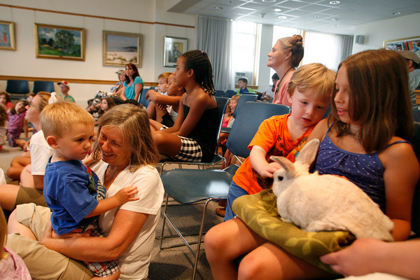 Rockport: Sam Coppi, 2, being held by his grandmother Cheryl Goodman looks at a bunny named Angel being held by Jordan Story, 8,  and her brother Austin, 3, during a presentation called Going Green With Your Pets at the Rockport Public Library Wednesday afternoon.  The program, which was part of the Summer Reading Program, talked about why it is better to adopt a pet rather than buy one or catch one in the wild and taught kids how to recycle household items to make toys for their pets. Mary Muckenhoupt/Gloucester Daily Times