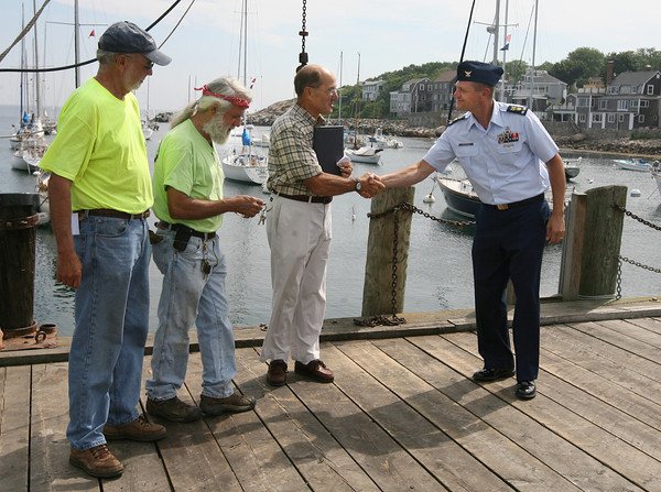 Rockport: Chris Sparkman of the U.S. Coast Guard shakes hands with Rockport Selectman Andrew Heinze as Paul St. Germain and Dr. Sidney Wedmore of the Thacher Island Association look on yesterday morning during a ceremony recognizing the transfer of the Straitsmouth Island lighthouse from the Coast Guard to the town of Rockport. The Thacher Island Association will manage the lighthouse. Photo by Kate Glass/Gloucester Daily Times