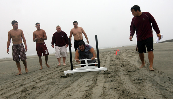 Gloucester: Coltyn Rivas, Gilbert Brown, Kyle Jenkins, Brian Ingersol and Dave Linquata cheer Andrew Porper on as he pushes the Prowler across the sand at Good Harbor Beach yesterday morning as part of Mike Lattof's conditioning clinic. Photo by Kate Glass/Gloucester Daily Times