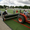 Manchester: Crews from Statewide Construction, including Howard Reed driving the backhoe, work to unroll a section of the turf field in front of Manchester Essex Regional High School Thursday morning.  The field is rolled out in sections and then sewn together. Mary Muckenhoupt/Gloucester Daily Times