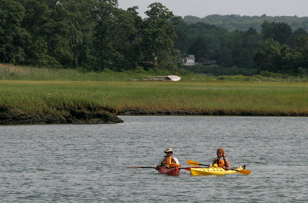 Gloucester: Bob and Diane Francis of Gloucester float down the Jones River past Long Wharf yesterday afternoon. The two waited for the rain to pass and then ventured out on their first kayaking trip of the season. Photo by Kate Glass/Gloucester Daily Times