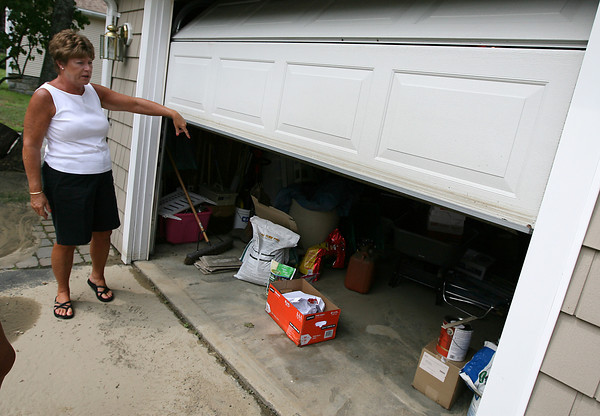 Gloucester: Sharon Lovasco points to marks along the bottom of her garage door left by several inches of sludge from a water main break across the street near Bayview Station yesterday morning. Photo by Kate Glass/Gloucester Daily Times