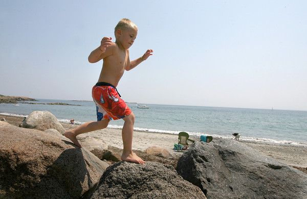 Rockport: Dylan Nelson walks across the rocks at Pebble Beach on Saturday after trying to sneak up on his sister, Jennifer, who was resting nearby. Photo by Kate Glass/Gloucester Daily Times