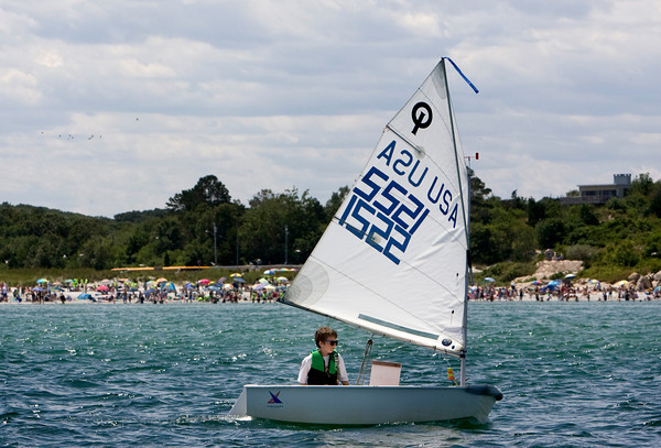 Gloucester:  Tristan Bannerman of the Sandy Bay Yacht Club sails past Wingaersheek Beach as he sets out for the race course before the 109th Annual Squam Day Invitational out of Annisquam Yaght Club Friday afternoon.  Mary Muckenhoupt/Gloucester Daily Times