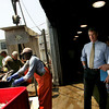 "Gloucester: Senator Scott Brown talks with former fisherman and fishing advocate Vito Calomo while crews unload a fresh catch at The Fish Auction Friday afternoon.  Brown made his first fact finding trip to the Gloucester fishing industry and pledged to organze ""serious"" hearings into law enforcement excesses. Mary Muckenhoupt/Gloucester Daily Times"