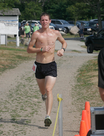 Gloucester: Tom Davis of Newton crosses the finish line of the Seventh Annual Seacoast 7 Road Race at Stage Fort Park on Saturday morning with a winning time of 37:55. Photo by Kate Glass/Gloucester Daily Times