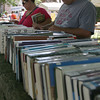 Manchester: Richard Brooks and Renee Retzlaff of Gloucester look through books lined up along the wall outside the Manchester Public Library during their book sale on Sunday. Photo by Kate Glass/Gloucester Daily Times