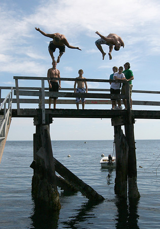 Gloucester: Dylan Spellman and Tim Surette do synchronized back flips off the Magnolia Pier as their friends watch. The pier is a popular spot for jumping near high tide. Photo by Kate Glass/Gloucester Daily Times