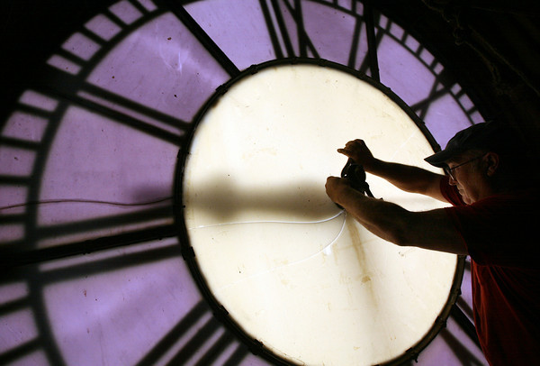 Gloucester: Tom Moore of Moore's Steeple People removes the old mechanical elements from one of the clock faces at Gloucester City Hall yesterday. The clocks are getting new hands and new motors as part of the building's restoration project. Photo by Kate Glass/Gloucester Daily Times