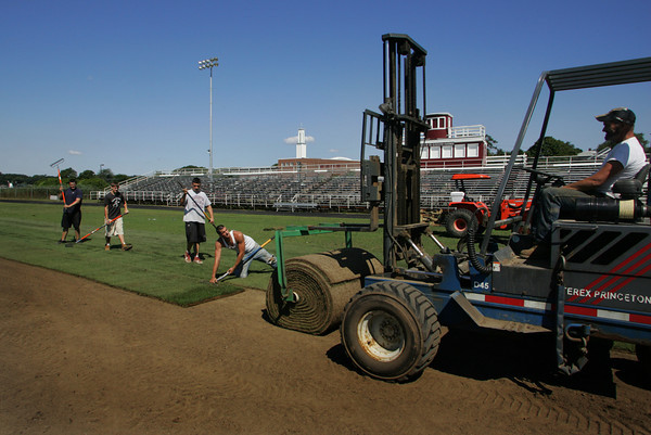 Gloucester: From left, upcoming seniors and football players Bryan Ingersoll, Josiah Bedrosian and Jordan Shairs along with Corey Frost, of Home Field Athletics work to resod Newell Stadium Friday afternoon.  The Gloucester Fisherman's Athletic Association paid to resoded the field, which hadn't been done in at least 12 years, because the condition of the field was unplayable. Driving the fork lift is Larry Senn. Mary Muckenhoupt/Gloucester Daily Times