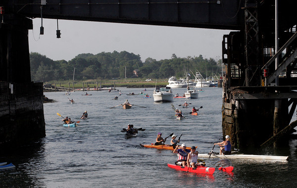 Gloucester: Rowers on a variety of boats, including outrigger canoes, kayaks, and dory boats, make their way under the railroad bridge to the start of the Blackburn Challenge, a 20-mile open water race around Cape Ann, on Saturday morning. Photo by Kate Glass/Gloucester Daily Times