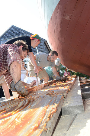 Essex:  Volunteer's first applied a coat of parafin wax and then grease to planking which helps the Ardelle slide easier on her side when launched into the Essex River Saturday afternoon at H.A Burnham. Desi Smith/Gloucester Daily Times. July 9,2011
