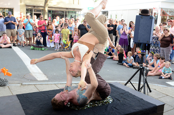 Gloucester: Alex and Jessamyn of Th' Bones and Roses Circus Sideshow performs their act on peices of glass before a large crowd at the Annual Block Party on Main St Saturday night. Desi Smith/Gloucester Daily Times. July16,2011
