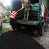 Conor Miller of Black Earth Hauler shovels compost onto a tarp for one of their clients. Photo by Kate Glass/Gloucester Daily Times