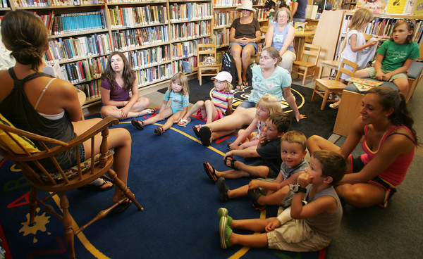 """Emily Stanton reads """"The Princess Who Had Almost Everything"""" to a group of children from the Magic Years Summer Adventure group at the Manchester Library during the """"One World, Many Stories"""" event. Photo by Maria Uminski/Gloucester Daily Times"""