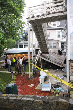 Gloucester: Detective Steve Mizzoni (stripped shirt) and other first responders look over a three story deck that collapsed around  7:45 pm at 119 Western Ave Sunday night. The electrical meter was ripped off the building and National Grid was called in,as well as the Gloucester Building and Elecrical Inspectors. No one was injured in the collapse.  Desi Smith/Gloucester Daily Times. July 3,2011