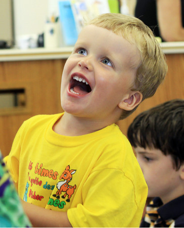 David Le/Gloucester Daily Times. Doron Appleyard, 3, of Essex talks excitedly with musician John Root at the TOHP Burham Library in Essex on Monday afternoon during A World of Music program. 7/11/11.
