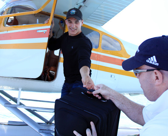 David Le/Gloucester Daily Times. Keith Deschambeault, owner and pilot of Acadian Seaplanes, of Rangeley Maine, left, is handed a suitcase from Zach Lehman, of Bethel, Maine, as they prepare to take off from Gloucester Harbor on Friday morning. 7/1/11.