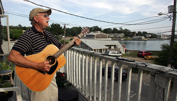 Ernie Pigeon serenades the people passing through the Rocky Neck art colony from a top the balcony of Elynn Kroger's art gallery. Photo by Maria Uminski/Gloucester Daily Times