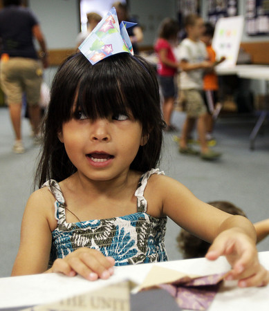 David Le/Gloucester Daily Times. Elaina Funk, 6, shows off an origami hat she just made at Origami Around the World held at the Gloucester Lyceum and Sawyer Free Library on Monday morning. 7/11/11.