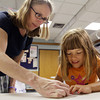 David Le/Gloucester Daily Times. Laura Geggis, of Topsfield, left, helps out Lotus Marsh, 5, to make an balloon at Origami around the world at the Gloucester Lyceum and Sawyer Free Library on Monday morning. 7/11/11.