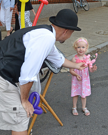 Gloucester: Joe Howard (AKA) The Ballon Man hands Scarlett Berge 2, a pink ballon poddle to match her dress at the Annual Block Party on Main St Saturday night. Desi Smith/Gloucester Daily Times. July16,2011