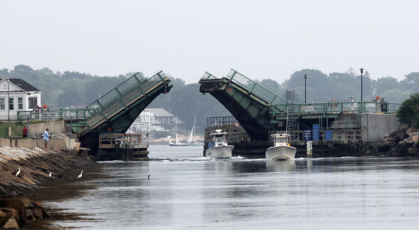 Boats pass under the Blynman Bridge as they head in from the harbor yesterday. Photo by Kate Glass/Gloucester Daily Times