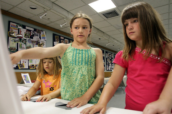 David Le/Gloucester Daily Times. Lila Olson, 9, center, and Sarah-Jean Collins, 7, right, work together to try and put together an Origami piece while Lotus Marsh, 5, left, works on a fold. 7/11/11.