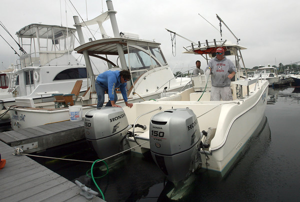Billy Pascucci of Essex hoses down the Cat-Fish at Cape Ann Marina after a day of fishing with David Marks of Florida, left, and Steve Landers of Hamilton yesterday morning. Photo by Kate Glass/Gloucester Daily Times