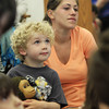 David Le/Gloucester Daily Times. Jake Zschau, 3, and Lydia French, of Manchester listen as guest musician John Root performs during A World of Music program held at the TOHP Burnham LIbrary on Monday afternoon. 7/11/11.