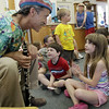 David Le/Gloucester Daily Times. Heather Adams, 8, right, and her brother Kevin, 6, center, talk with guest musician John Root after he played them a song on the clarinet during A World of Music program at the TOHP Burnham Library in Essex on Monday. 7/11/11.
