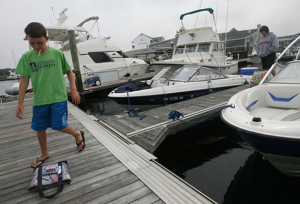 Bobby Dunn, 9, of Quincy, helps his mom, Lisa Dunn, unload stuff from their boat at Cape Ann Marina yesterday. Photo by Kate Glass/Gloucester Daily Times