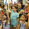David Le/Gloucester Daily Times. Heather Adams, 8, left, and Isabella Thurlow, 7, both of Essex raise their hands to tell musician John Root what they just heard, while Jake Zschau, 3, of Manchester, covers his ears from the noise. A World of Music program was held Monday afternoon at the TOHP Burnham Library in Essex. 7/11/11.