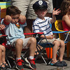 Logan Guittarr, left, blocks his ears as his cousin, Tucker Nichols, waves to the fire trucks as they head up School Street during the Manchester 4th of July Parade yesterday morning. Photo by Kate Glass/Gloucester Daily Times