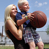David Le/Gloucester Daily Times. Vlade Ouellette, 5, of Gloucester, smiles as he prepares shoot the basketball while being held up by his nanny, Devin Foley, also of Gloucester, at Fort Point Park on Wednesday morning.7/13/11.
