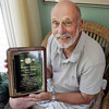 "David Le/Gloucester Daily Times. Rockport ""Citizen of the Year"" recipient, Frank Hassler, displays the plaque awarded to him in his Rockport home on Monday afternoon. 7/11/11."