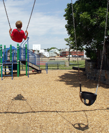 David Le/Gloucester Daily Times. Dru Ouellette, 8, of Gloucester swings himself high in the air on the playground at Fort Point Park on Wednesday morning. 7/13/11.