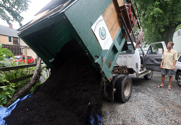 Conor Miller of Black Earth Hauler unloads compost at a client's home. Parts of the truck's lift system are made with recycled marine parts. Photo by Kate Glass/Gloucester Daily Times