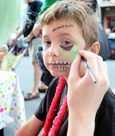 Gloucester:Jonathan Spada 7, of Gloucester gets a new face painted on by Kyle Rowe of Island Art and Hobbies at the Annual Block Party on Main St Saturday night. Desi Smith/Gloucester Daily Times. July16,2011