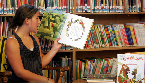 "Emily Stanton reads ""The Princess Who Had Almost Everything"" during Manchester Library's ""One World, Many Stories"" story time. ""One World, Many Stories"" story time takes place every Tuesday in July at the Manchester Library. Photo by Maria Uminski/Gloucester Daily Times"