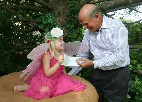 Ella Hammer, 5, hands a check for $1,040 to Richard Lorigan of Cape Ann Habitat for Humanity. The money was raised during Underwood Photography's Annual Faery Festival, which was held in June. Photo by Kate Glass/Gloucester Daily Times